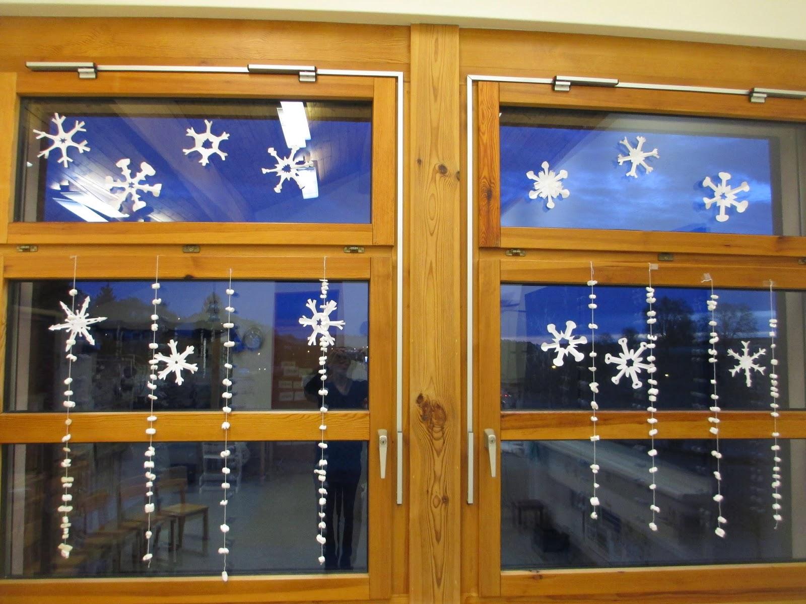 Schneeflocken und Girlanden am Fenster