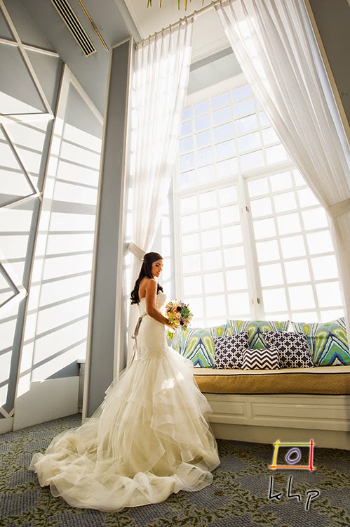 Gorgeous bride posing in front of the large windows of the Portofino Hotel's elegat lobby