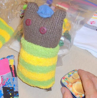 Cylindrical stuffed toy, cut out of brown sweater fabric with ears to suggest a cat's head. The eyes are two buttons and it wears a blue hat between its ears. The body is covered by a length of pale green and yellow-striped sock material. In the right foreground, a human hand holds a small metal box with an orange tabby cat painted on the lid.
