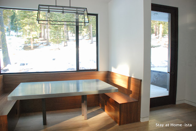 Window wrapped dining nook with walnut benches and a zinc table