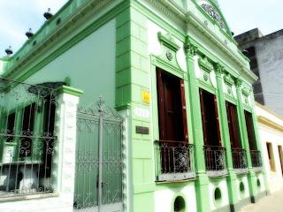 Casarão Cândido Norberto Leite Lopes, em Bagé. Antiga casa, verde clara, com quatro janelões frontais e entrada pela lateral.