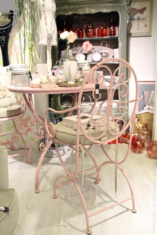 verschnörkelter Eisenstuhl in rosa vor einem runden Tisch mit Deko
