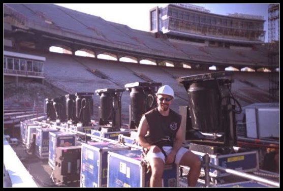 Tom Bowser sitting on a road case during setup for the Rolling Stones Voodoo Lounge Tour at Camp Randall Stadium in Madison, WI