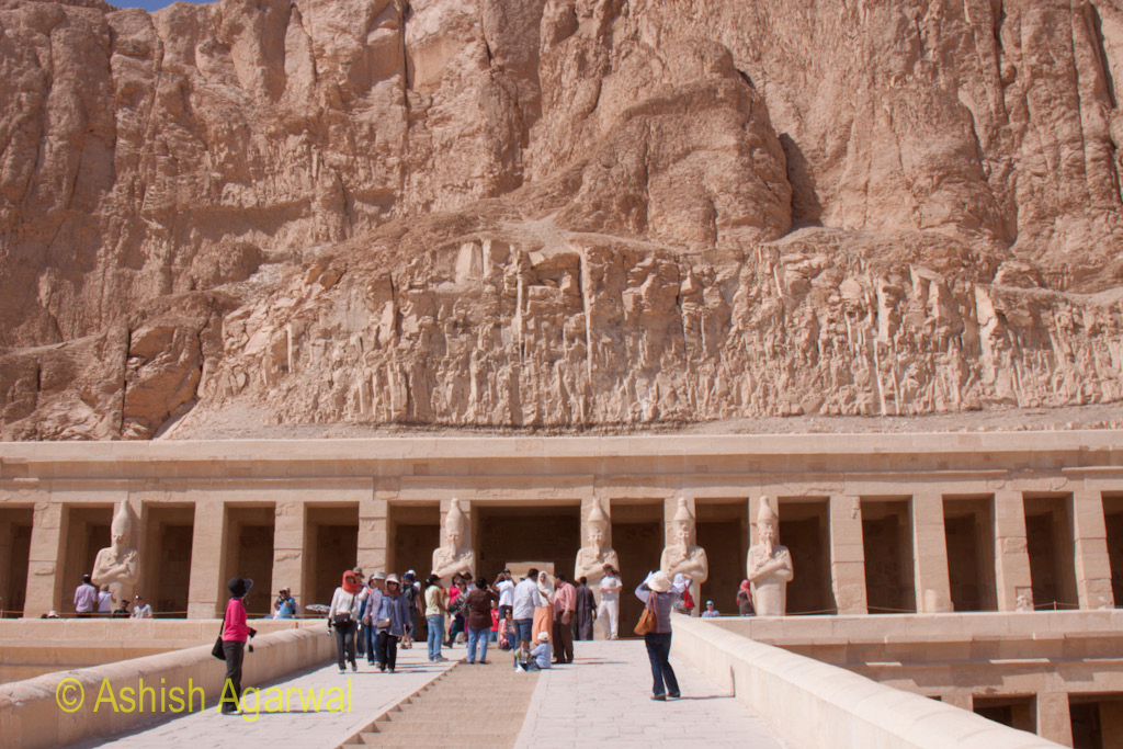 View of tourists on the upper sections of the Hatshepsut temple, along with the cliffs on top of the temple