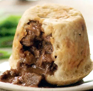 Classic steamed steak and kidney pudding with rich gravy in a suet crust