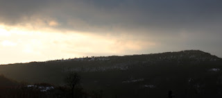 The ridge, contrasting darkly with the sun