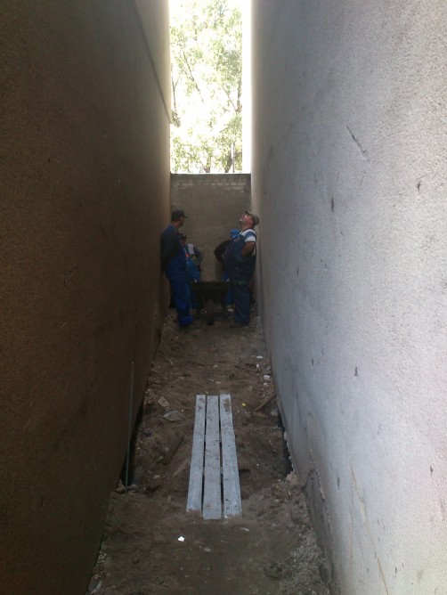 Picture of three workers digging hole for the narrowest house foundation
