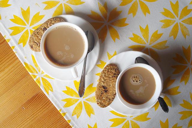 Zwei Tassen Kaffee auf Tischläufer mit gelben Blüten