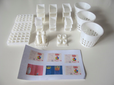 Selection of 3d-printed modern dolls' house miniatures, including storage containers, waste baskets and spray cans.