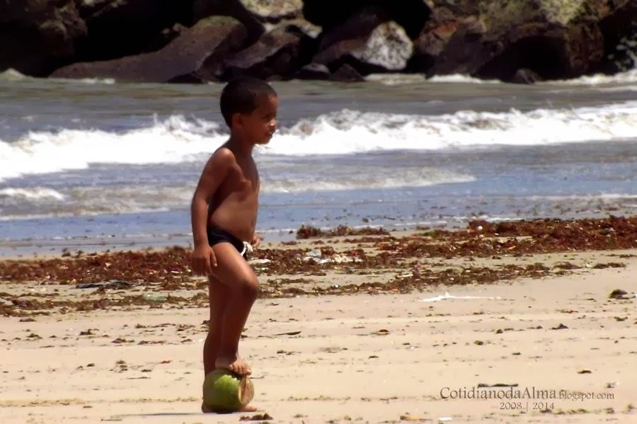 Criança jogando futebol com coco
