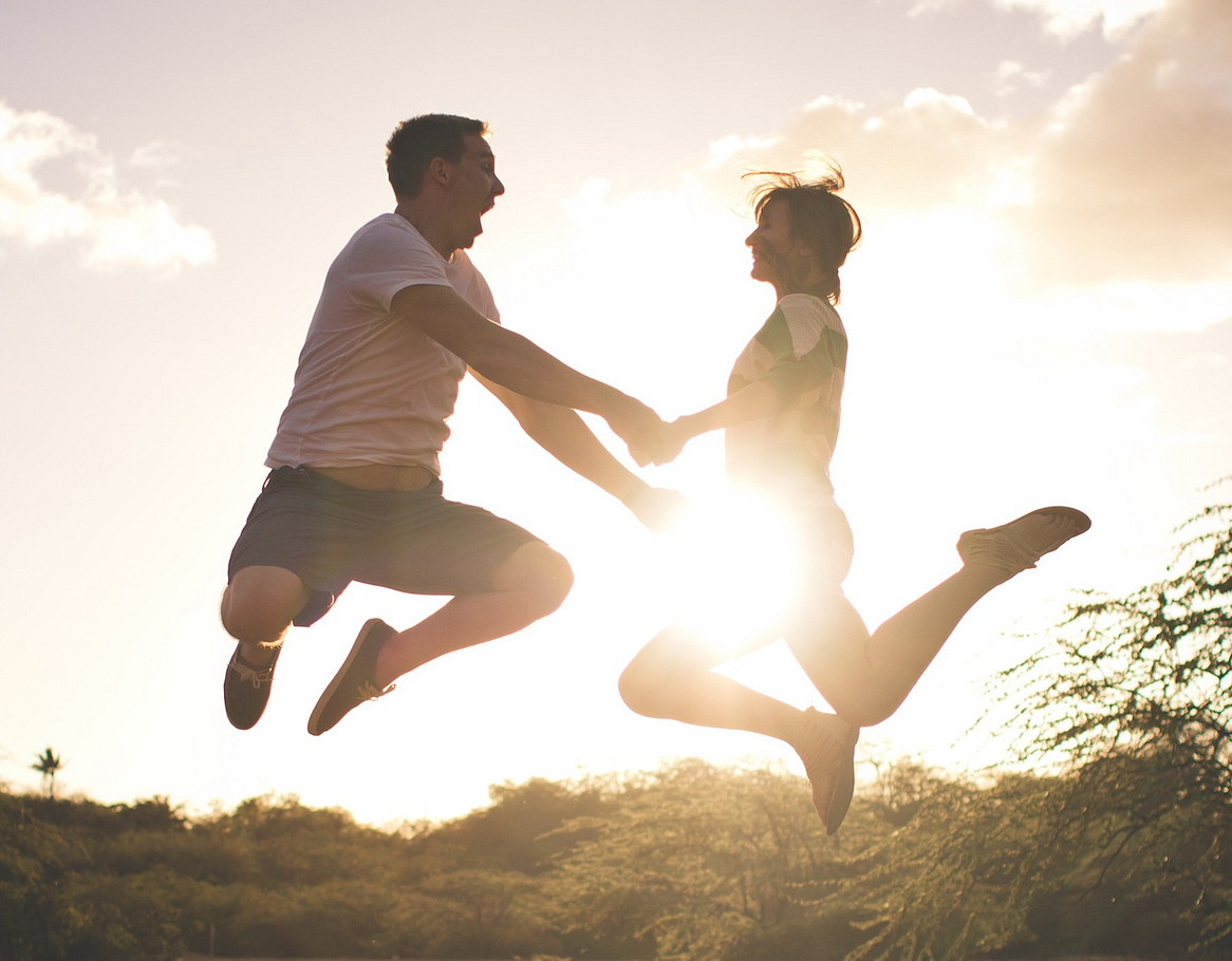Man and woman holding hands and jumping with the sun behind them