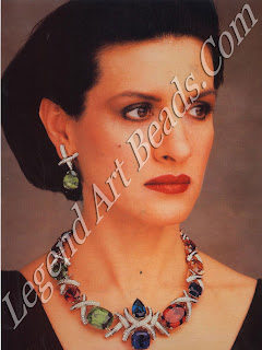 Paloma Picasso wearing an elaborate Tiffany set of necklace and earrings, set with a wide selection of precious and semi-precious stones.