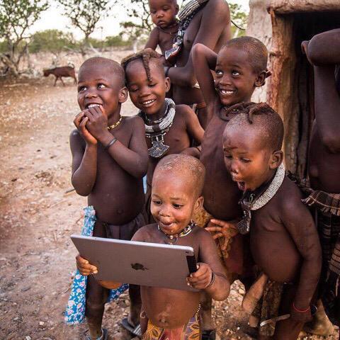 Crianças africanas admirando aparelho da Apple