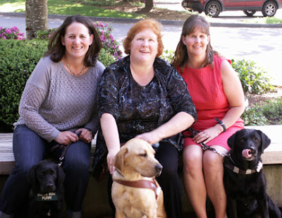 Megan, Laura Ann and Cathy sit smiling on a bench with their dogs