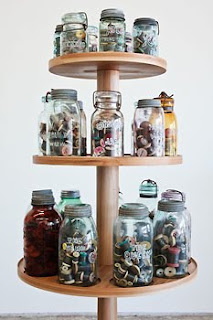 Three tiers of jars filled with spools of thread