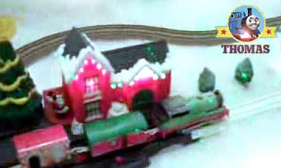 TrackMaster Thomas train travels chilly snow coated rail tracks towards decorative railway station