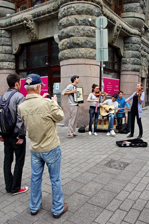 Grupo musical a tocar em plena rua e um homem a tirar fotografias