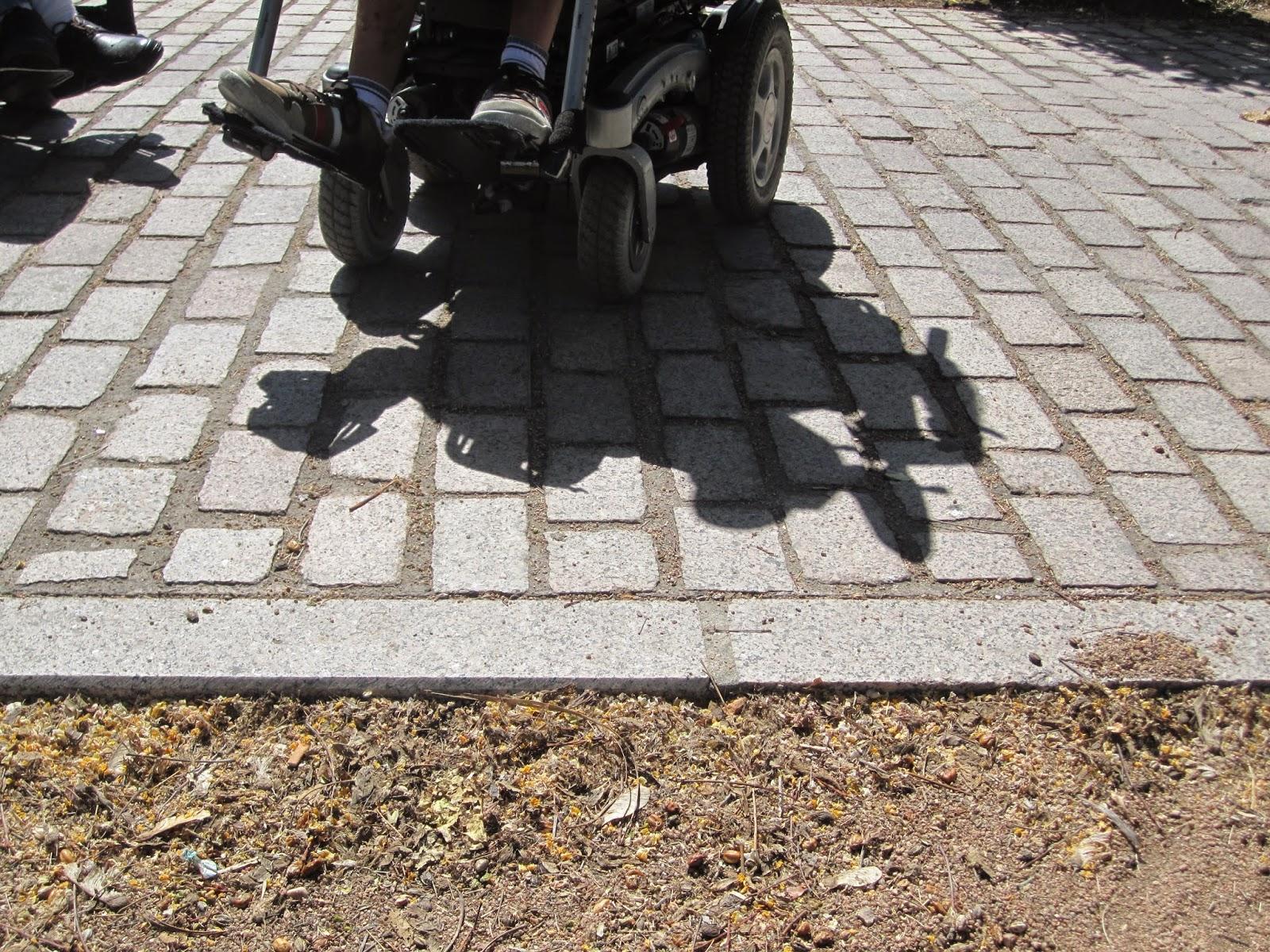 Se aprecia a un usuario de sillas de ruedas sobre la superficie adoquinada y frente al desnivel oculto.