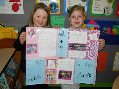 Avery and Natalie (smiling) hold up their school project together