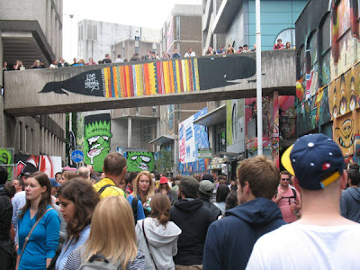 Crowds walking between concrete walls that have been painted with brightly colored graffiti-style images, varying greatly