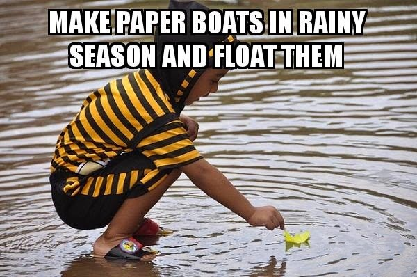 kid floating paper boat in rain water