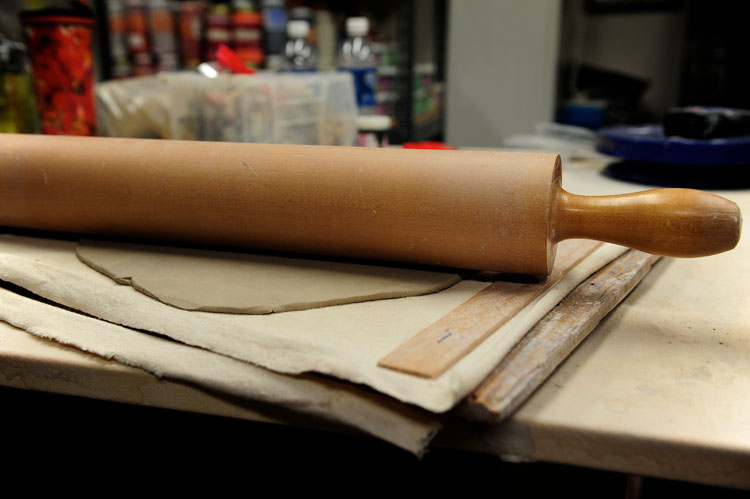 A rolling pin on a canvas wrapped board with guides will help you get an even thickness when you roll out the clay. 