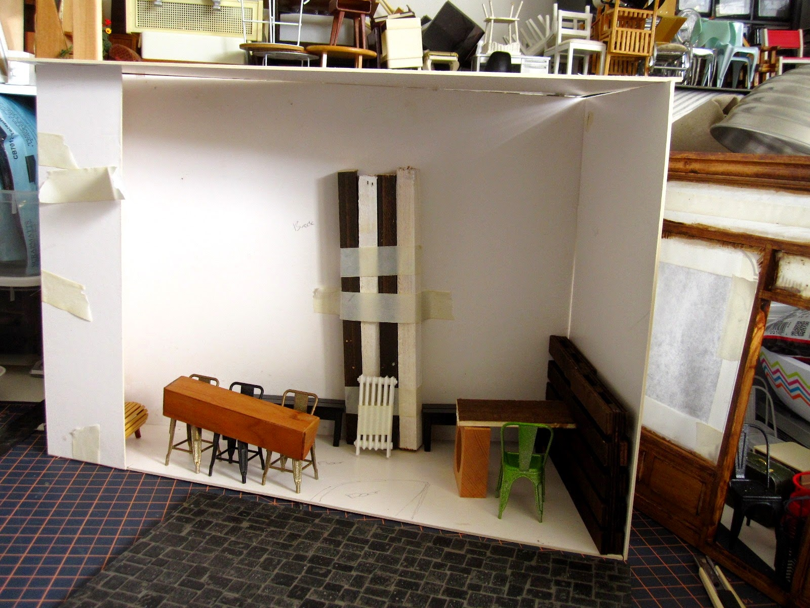 Modern dolls' house miniature cafe, half built with furniture arranged in a cardboard room.