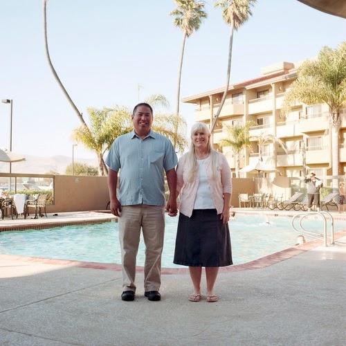 Nesta foto um casal em frente a piscina, ela veste uma saia, e ele uma camisa e calça social.