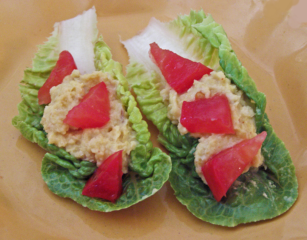 Tiny Lettuce Leaves Topped with Hummus and Tomatoes