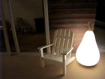 Dry fit of a dolls' house shed kit at night, with an Adirondack chair and a light-up pear sculpture outside it.
