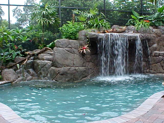 Home and garden artificial rocks around swimming pool for Rock waterfall