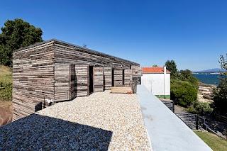 Casa Revestida con Cajas Recicladas de Madera