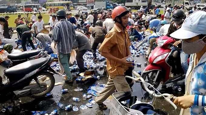 Nhiều người cùng lấy bia do xe chở bia làm đổ ra đường - Ảnh cắt từ clip bạn đọc quay được