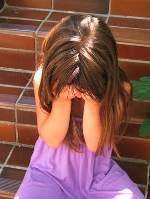 NAMC montessori crying in the classroom girl on steps holding face