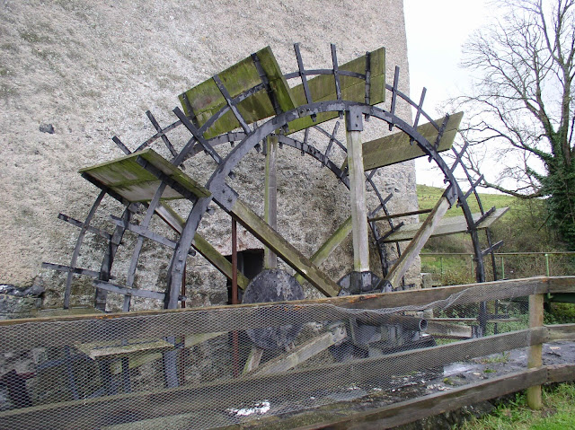 close up of a water wheel against an old stone wall
