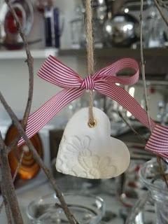 λευκή ανάγλυφη καρδούλα με κόκκινη κορδέλα