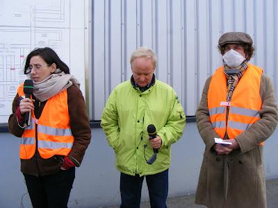 Menschen in grellfarbenen Schutzwesten, Dolmetscherin, PR-Mensch der Mülltrennungsanlage, Dozent mit Mundschutz