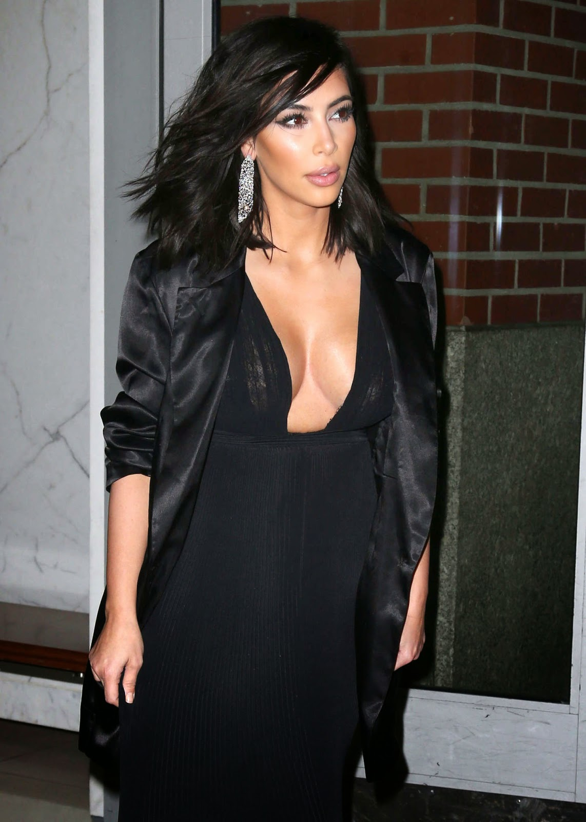 Kim Kardashian in a pleated plunging black maxi dress out and about in NYC