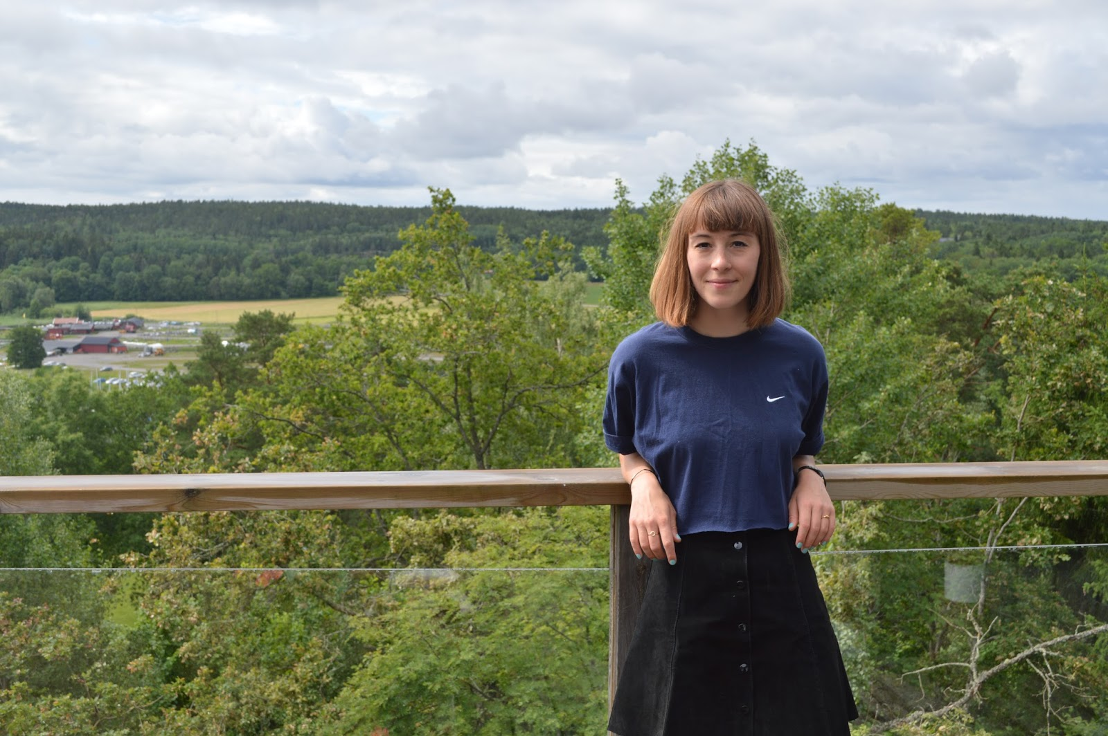 Me in retro Nike t-shirt and suede button down skirt with view from Airbnb Swedish cabin