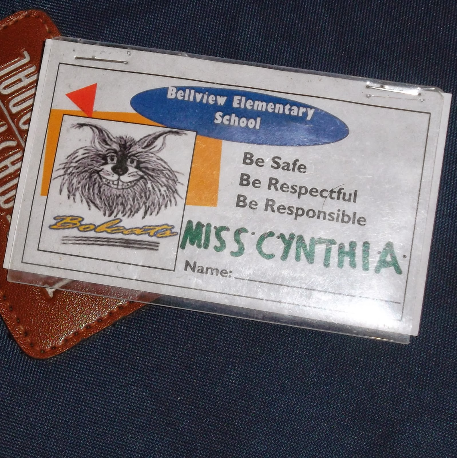 "Business-card sized piece of paper reading ""Bellview Elementary School. Be Safe. Be Respectful. Be Responsible,"" displaying line-drawn image of the school's Bobcat mascot. ""Miss Cynthia"" is hand-written above a space to write in a name, and the entire ticket is enclosed inside a clear plastic ID holder."