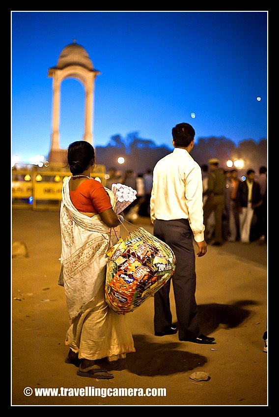 A female hawker selling some chips at India gate in Delhi (INDIA). There are lot of such options like chana-jor-garam, Golgappas, bhel-puri etc... All these folks do find some buyers and it is good that these people get to earn their livings as well. The only problem is cleanliness around the place. People find it too tough to walk to one of the abundant dustbins in the area to dispose of their plastic wastes and instead prefer to leave it lying in the green grass or on the roads... although people get everything cleaned next morning but over the time these places have become stinky and all the greenery has been ruined due to these bad habbits. Recently I read a very good article on Ghumakkar -