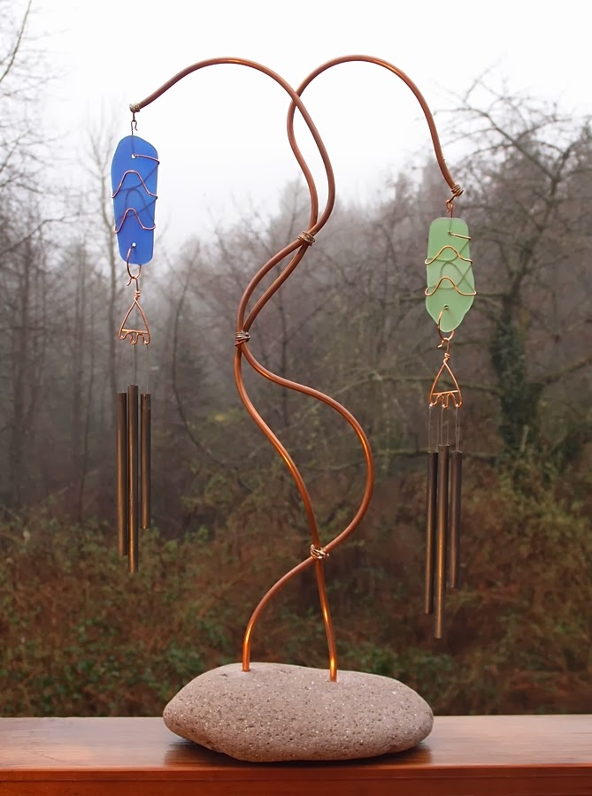 A freestanding double wind chime with glass, copper, and a natural beach stone.