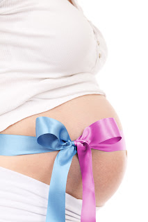 Pregnant belly with a blue and pink ribbon