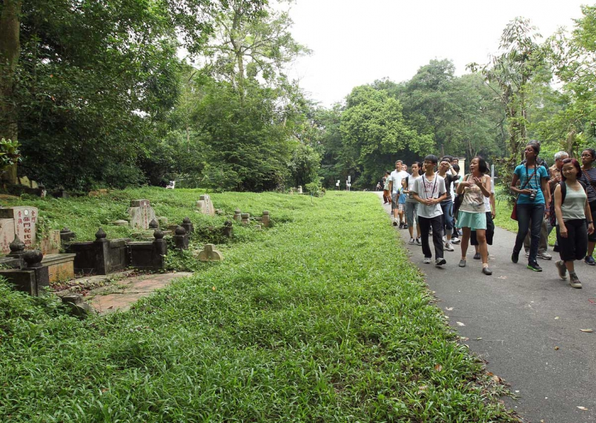 Volunteer guides leading visitors on a walk at Bukit Brown cemetery on July 13, 2013.