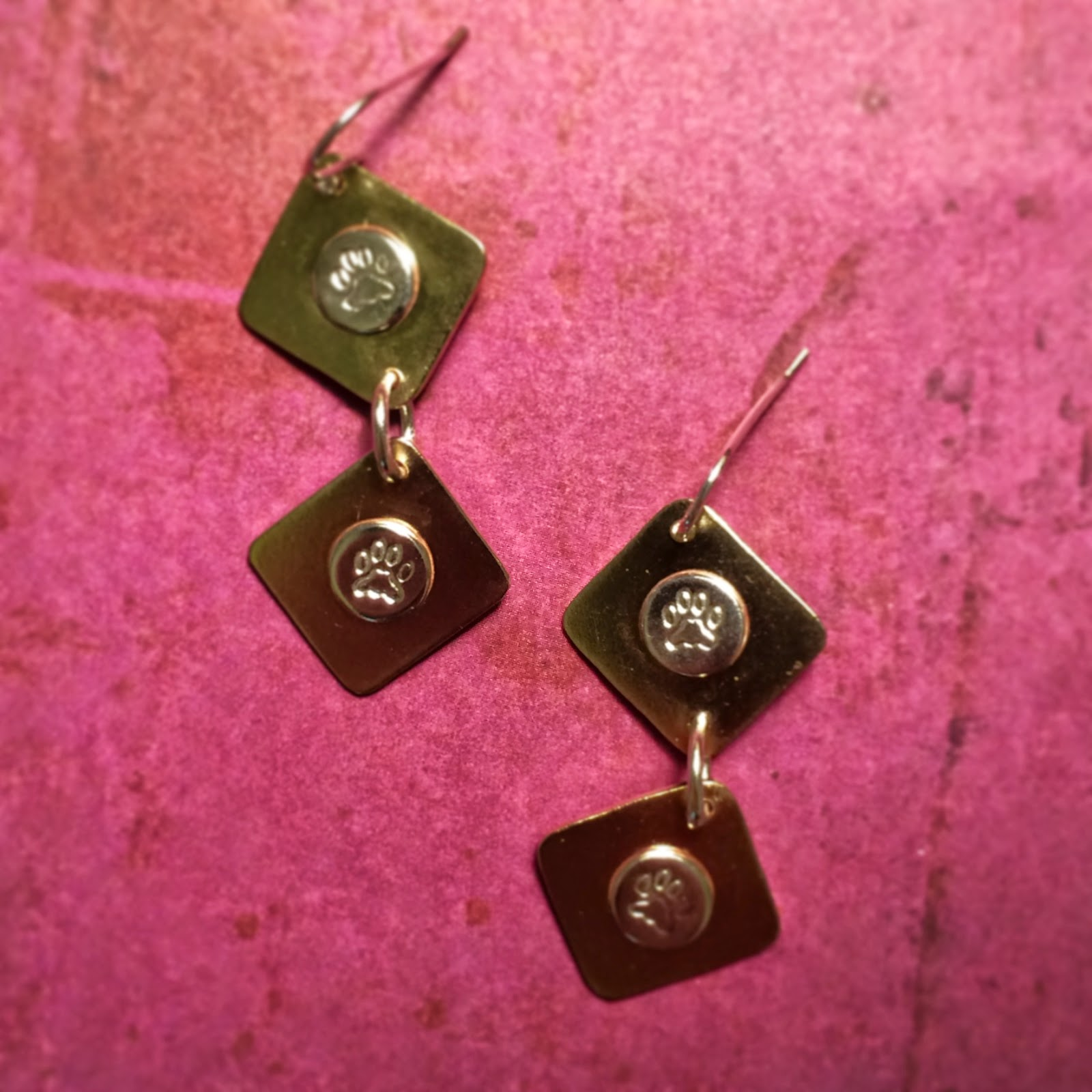 Earrings made with brass and silver with paw print stamps and soldered