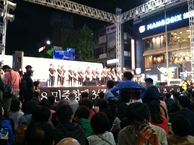 image of stage and crowd at outdoor ceremony in evening