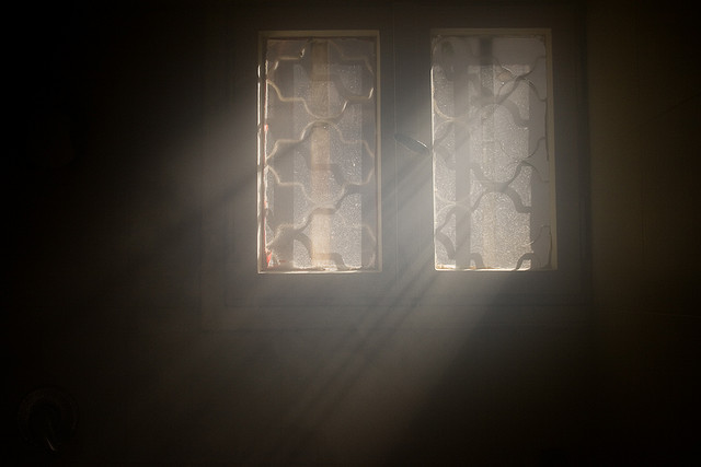 light shining into a dark room through leaded glass window