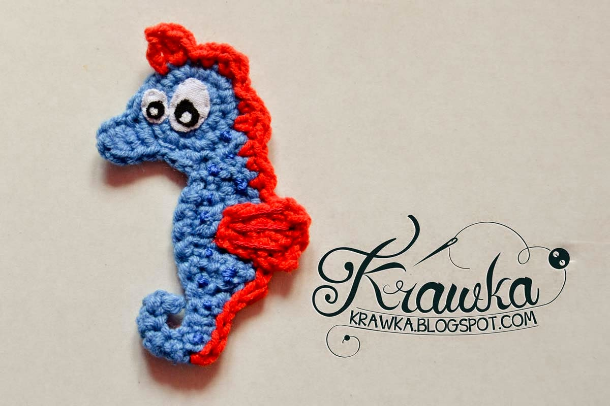 Crochet amigurumi application/stripe blue sea horse with red fins.