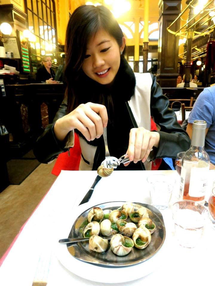 Asian Girl eating Escargots in Paris, France