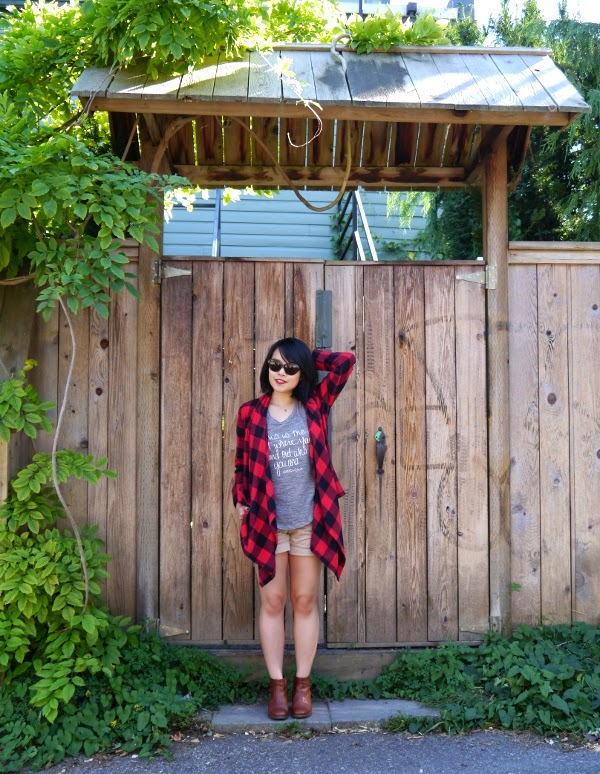 Summer to fall transitional dressing: buffalo plaid wrap, heather grey tank, khaki shorts, cognac ankle boots, and cat-eye sunnies.